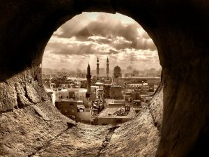 a sepia image of Cairo, seen through a round window