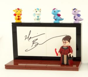 A Lego minifig of Lady Trent before a chalkboard with small dragons on top